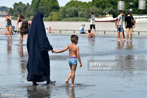 A woman wearing a chador walks with a young boy on the 'Mirroir d'eau' a reflecting pool of water in Bordeaux where temperatures came close to 40 C...