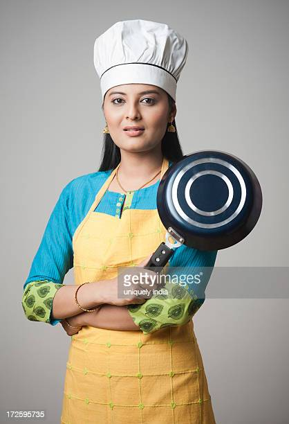 Woman wearing a chefs hat standing with his arms crossed holding a frying pan