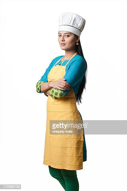 Woman wearing a chefs hat standing with his arms crossed