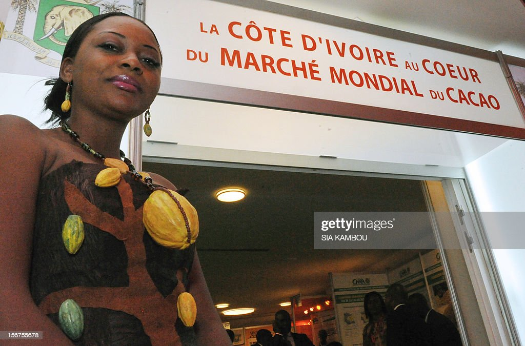 A woman wearing a collar made of cocoa pods, poses on November 20, 2012, in Abidjan, in front of the building which hosted the first World Cocoa Conference which opens today. The London-based International Cocoa Organisation (ICCO) organised the event to discuss a sustainable future for the industry in the face of growing demand. The conference is of particular interest to Ivory Coast, which is the world biggest producer of cocoa. ICCO said Africa in particular was a key area for the cocoa industry, with countries there expected to produce 70 percent of the world cocoa output for 2011-2012 that the ICCO estimates at nearly four million tonnes. Placard reads