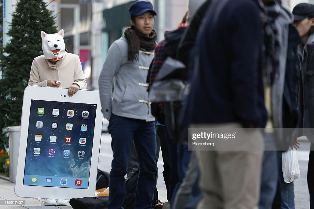 A woman, wearing a dog mask, uses a mobile device while holding a giant cardboard copy of an iPad as she waits in line with other customers outside an Apple Inc. store ahead of the launch of the company's iPad Air in the Ginza district of Tokyo, Japan, on Friday, Nov. 1, 2013. Apple Inc.'s forecast for the slowest holiday sales growth in a half decade reflects how iPhones and iPads arent providing the growth surges they once did as competition accelerates in the saturated mobile market. Photographer: Kiyoshi Ota/Bloomberg via Getty Images