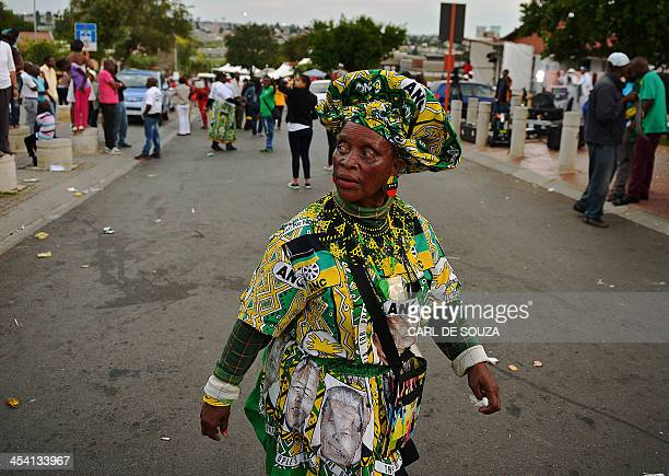 A woman wearing a dress with an ANCthemed motif walks near late former South African president Nelson Mandela's former home in the Orlando West...