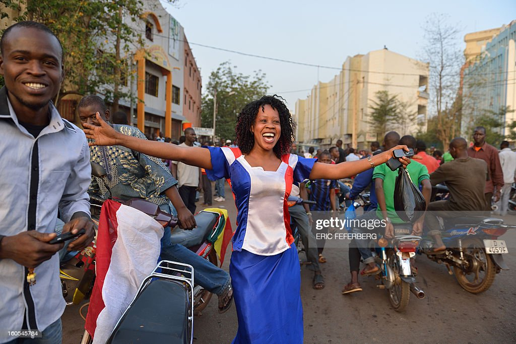 A woman, wearing a dress with the colors of the French national flag, dances on the Independance square during the visit of French President in Mali on February 2, 2013 in Bamako. French President Francois Hollande called on Africans to take over the fight against extremism as he received a rapturous welcome today in Mali, where a French-led offensive has driven back Islamist rebels from the north. AFP PHOTO / ERIC FEFERBERG