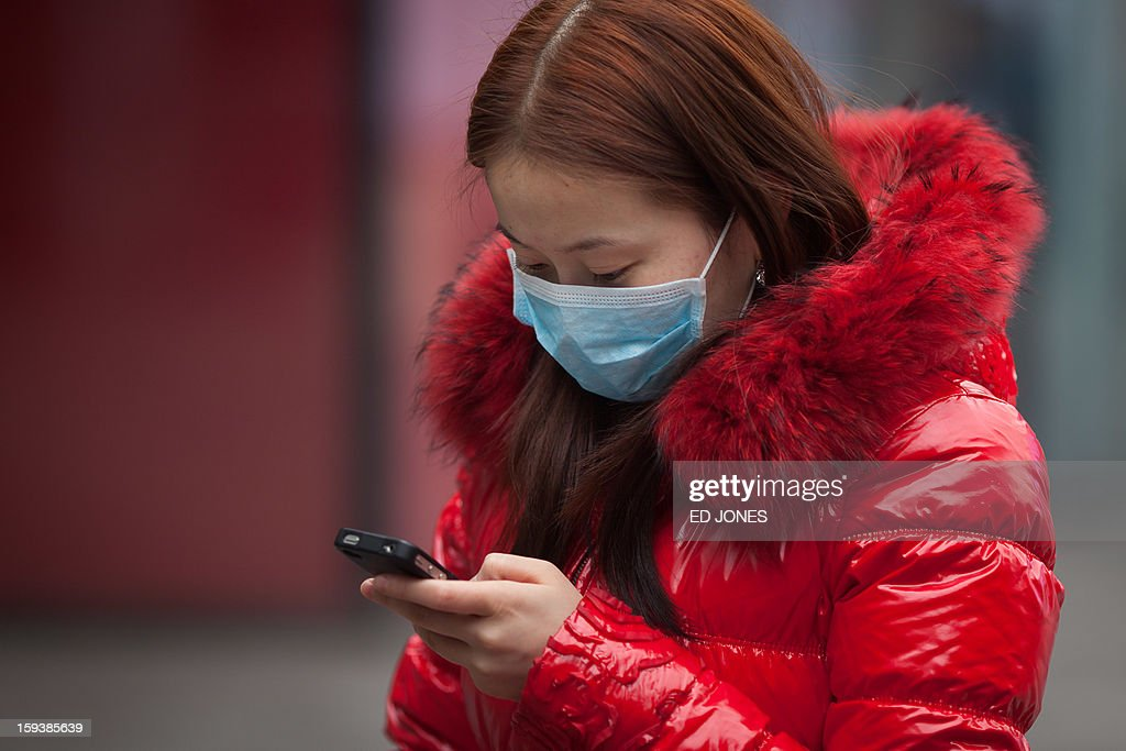 A woman wearing a face mask checks her phone during polluted weather in Beijing on January 13, 2013. Dense smog shrouded Beijing, with pollution at hazardous levels for a second day and residents advised to stay indoors, state media said. AFP PHOTO / Ed Jones