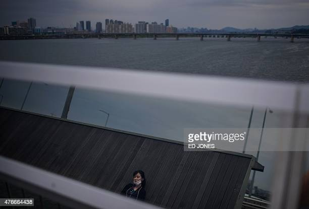 A woman wearing a face mask is reflected in a barrier as she sits on a viewing deck on the Mapo bridge over the Han river before the Seoul city...