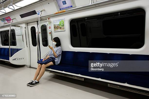 A woman wearing a face mask looks at her smartphone as she rides onboard a subway train in Seoul South Korea on Monday June 8 2015 South Korea...
