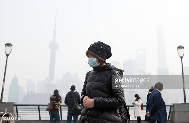 A woman wearing a face mask on a heavily polluted day stands along the Bund in front of the financial district of Pudong in Shanghai on December 15...