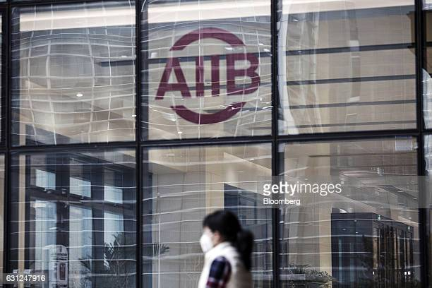 A woman wearing a face mask walks past a logo displayed at the Asian Infrastructure Investment Bank headquarters building in Beijing China on...