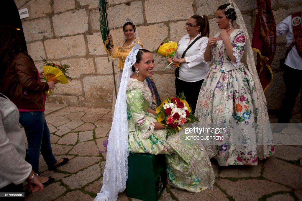A woman wearing a 'Fallera', a traditional dress of Valencia, takes part in the Romeria of the Virgen de la Cabeza, an annual religious pilgrimage, in Andujar, near Jaen, southern Spain, on April 27, 2013. Each year, thousands of devotees in traditional outfits travel from all over the country to the Sanctuary of the Virgin de la Cabeza during the pilgrimage, which is considered to be the most ancient Romeria in Spain.