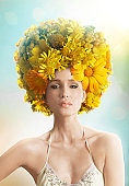 Woman wearing a fancy yellow hat made of flowers