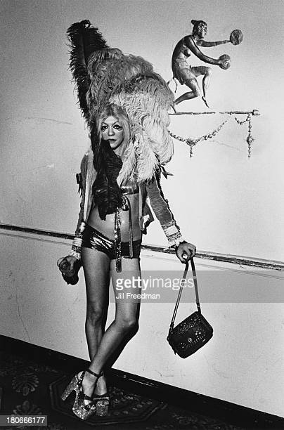 A woman wearing a feather headdress and hotpants poses at a Halloween party in a Midtown Manhattan hotel New York City 1973