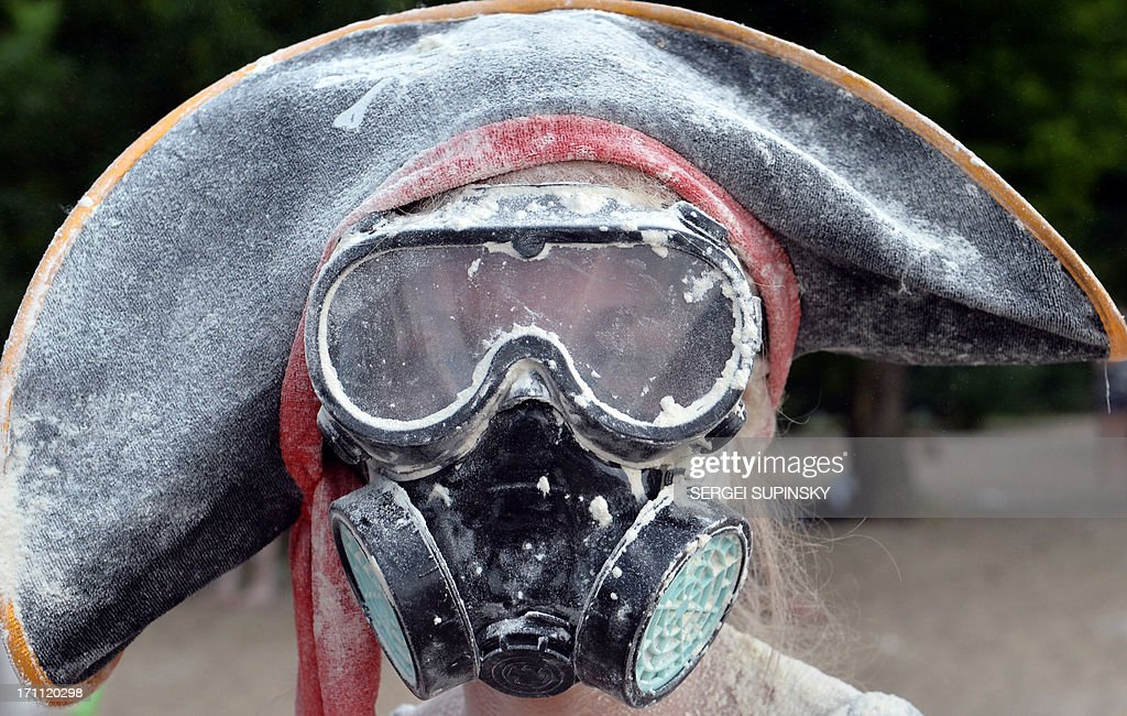 A woman wearing a gas mask covered wih flour poses during a happening called ''Battle With Flour'' in Kiev on June 22, 2013. Hundreds of young Ukrainians entertain themselves organizing events using social networks. AFP PHOTO/ SERGEI SUPINSKY