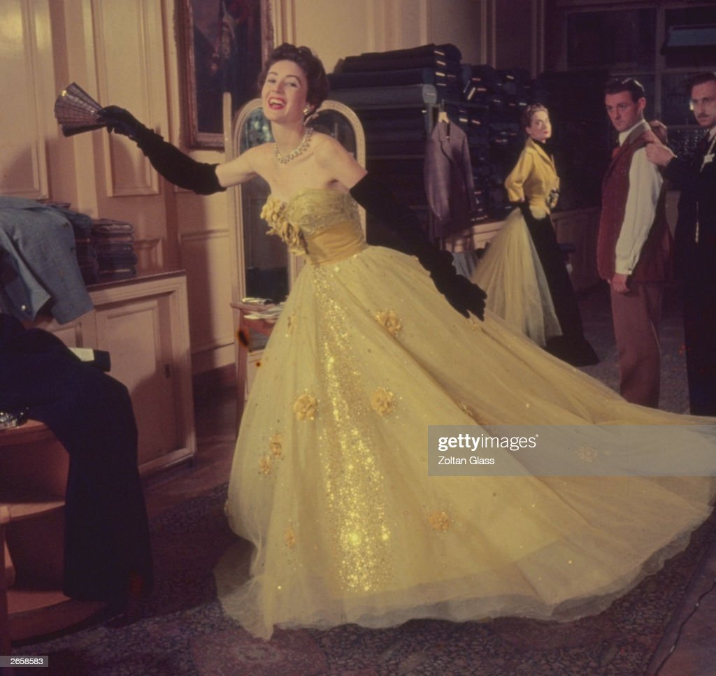 A woman wearing a gold evening dress with long black gloves and pearls in a tailor's shop Original Publication Picture Post 6054 Fashion It's A Man's...
