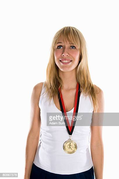 A woman wearing a gold medal and smiling