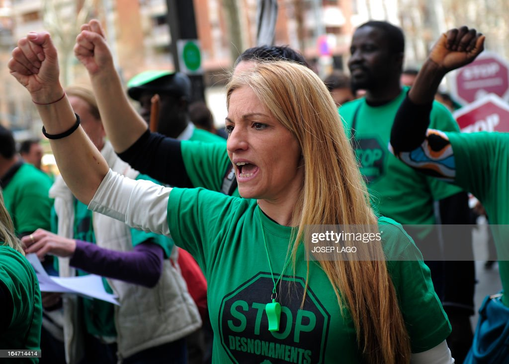 A woman wearing a green tshirt reading 'Stop evictions' gestures during a protest by Platform for Mortgage Victims (PAH) to push for a new law to end a wave of evictions of homeowners ruined by the economic crisis, in Barcelona, on March 27, 2013.