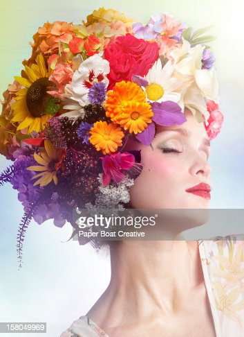 woman wearing a hat made of colorful flowers : Stock Photo