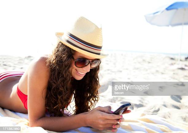 A woman wearing a hat on the beach while on her phone