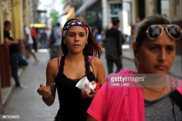 A woman wearing a headband with the US national flag walks along a street of Havana on October 27 2017 Almost drowned by the crisis of the 90s the...