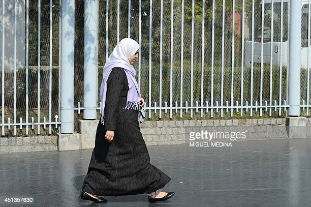 A woman wearing a hijab an islamic veil walks in a street on April 15 2010 in Nanterre outside Paris French government will pass a law to ban Muslim...