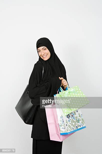 A woman wearing a Hijab and holding shopping bags