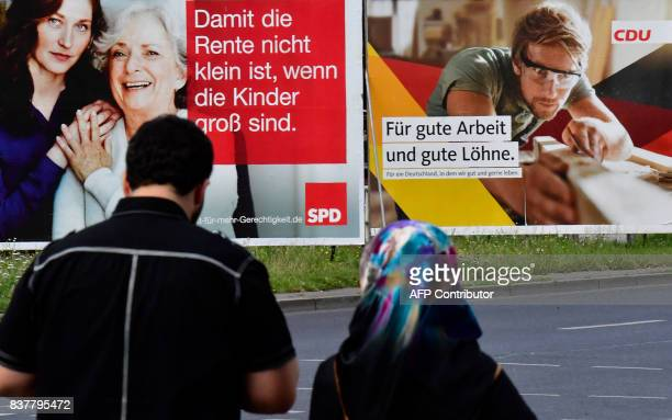 A woman wearing a hijab passes by several election banners for the upcoming September general elections in Berlin on August 23 2017 turkish President...