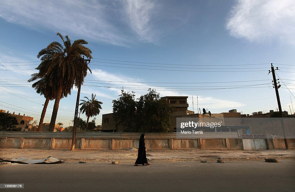 A woman wearing a hijab walks down a street on December 12, 2011 in Baghdad, Iraq. Iraq is transitioning nearly nine years after the 2003 U.S. invasion and subsequent occupation. American forces are now in the midst of the final stage of withdrawal from the war-torn country. At least 4,485 U.S. military personnel have died in service in Iraq. According to the Iraq Body Count, more than 100,000 Iraqi civilians have died from war-related violence.