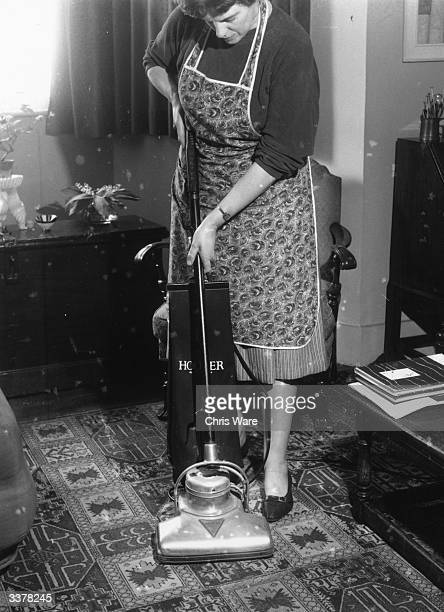 A woman wearing a housework apron cleaning her carpet with an upright Hoover vacuum cleaner