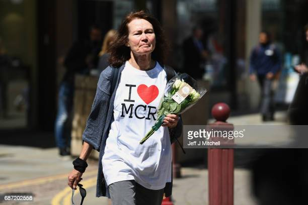 A woman wearing a 'I heart MCR' tshirt makes her way to lay flowers in St Ann Square on Tuesday May 23 2017 in ManchesterEngland At least 22 people...