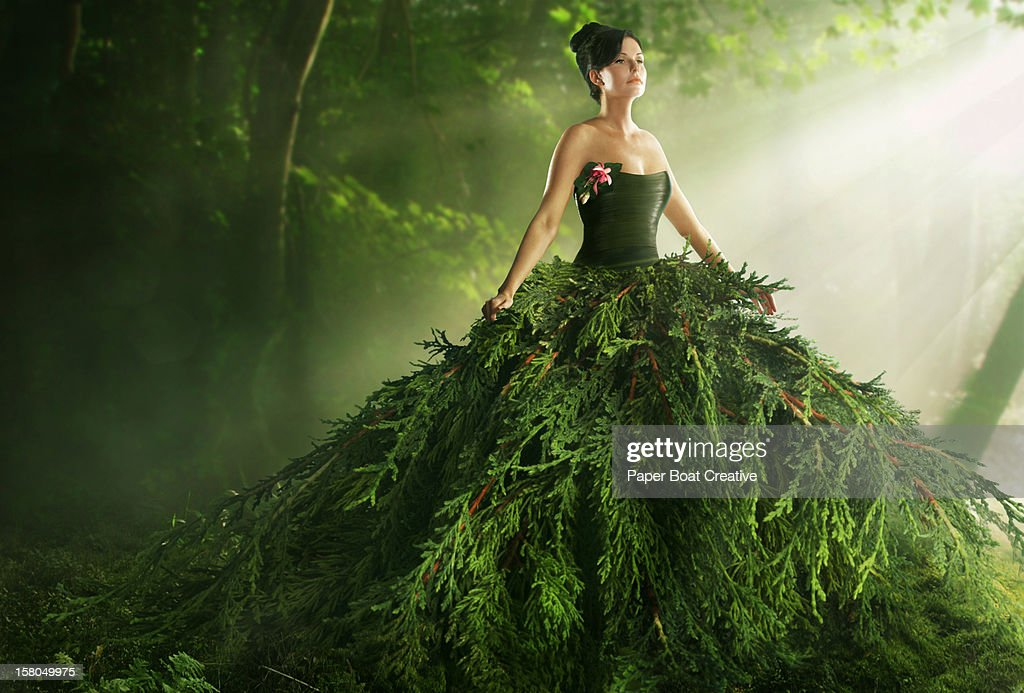 woman wearing a large green gown in the forest : Stock Photo