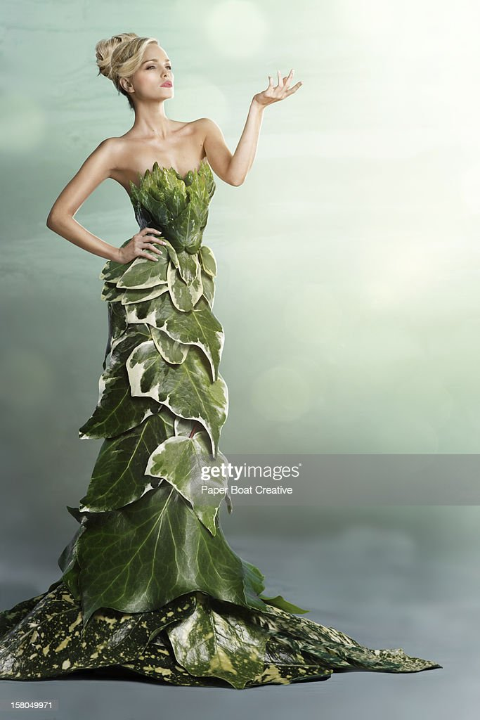 Woman wearing a long gown made of leaves