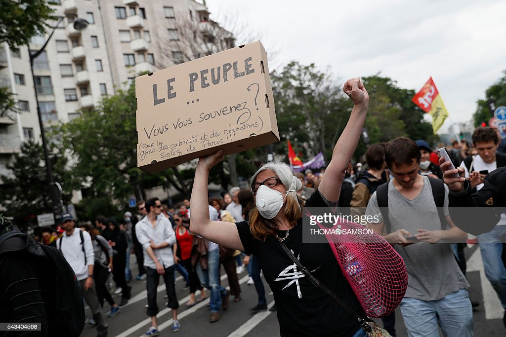 A woman wearing a mask and holding a carboard reading 'The People.. Do you remember?' takes part in a demonstration against controversial labour reforms, on June 28, 2016 in Paris. Unions have called repeated strikes and marches in opposition to the law, which seeks to bring down France's intractable 10-percent unemployment rate by making it easier to hire and fire workers. / AFP / Thomas SAMSON