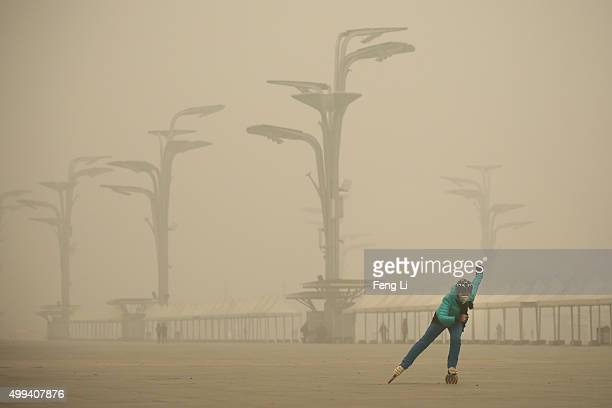 A woman wearing a mask practices roller blading at Olympic Park during dheavy smog on December 1 2015 in Beijing China The representatives of the...