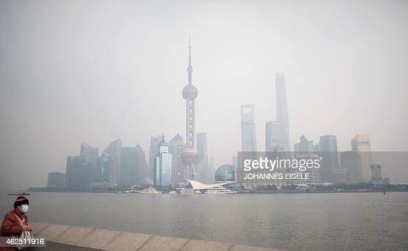 A woman wearing a mask stands on the promenade on the Bund overlooking the Huangpu River against the skyline of the Pudong district in Shanghai on a...