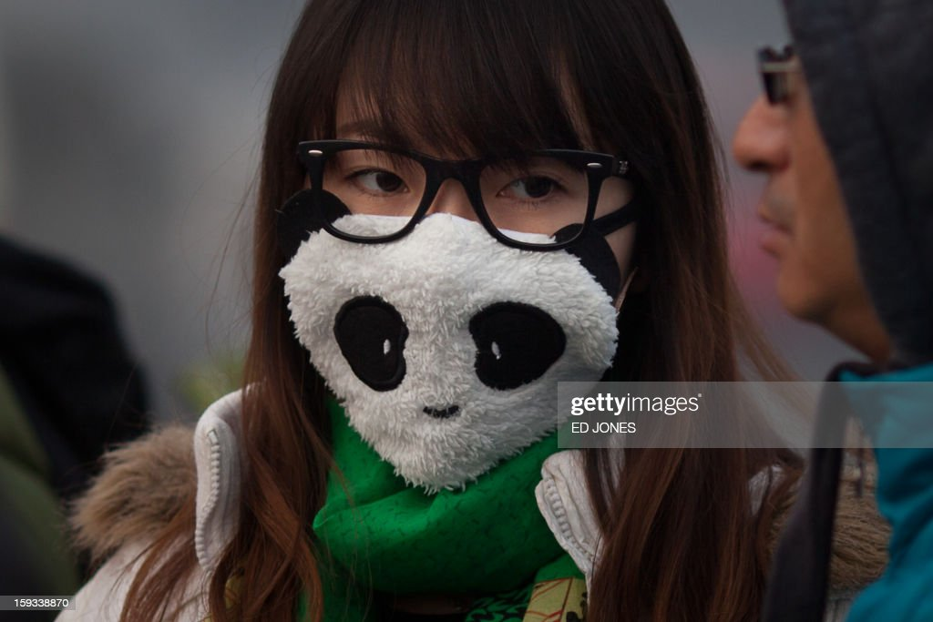 A woman wearing a mask walks on a street during severe pollution in Beijing on January 12, 2013. Air quality data released via the US embassy twitter feed recorded air quality index levels so hazardous that they were classed as 'Beyond Index'. By 4pm the particle matter (PM) 2.5 figure was 728 on a scale that stops at 500 at which point the US embassy website advises against all outdoor activity. AFP PHOTO / Ed Jones