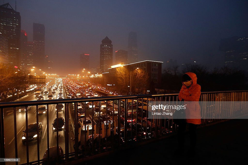 A woman wearing a mask walks on the street during severe pollution on January 23, 2013 in Beijing, China. The air quality in Beijing on Wednesday hit serious levels again as smog blanketed the city.