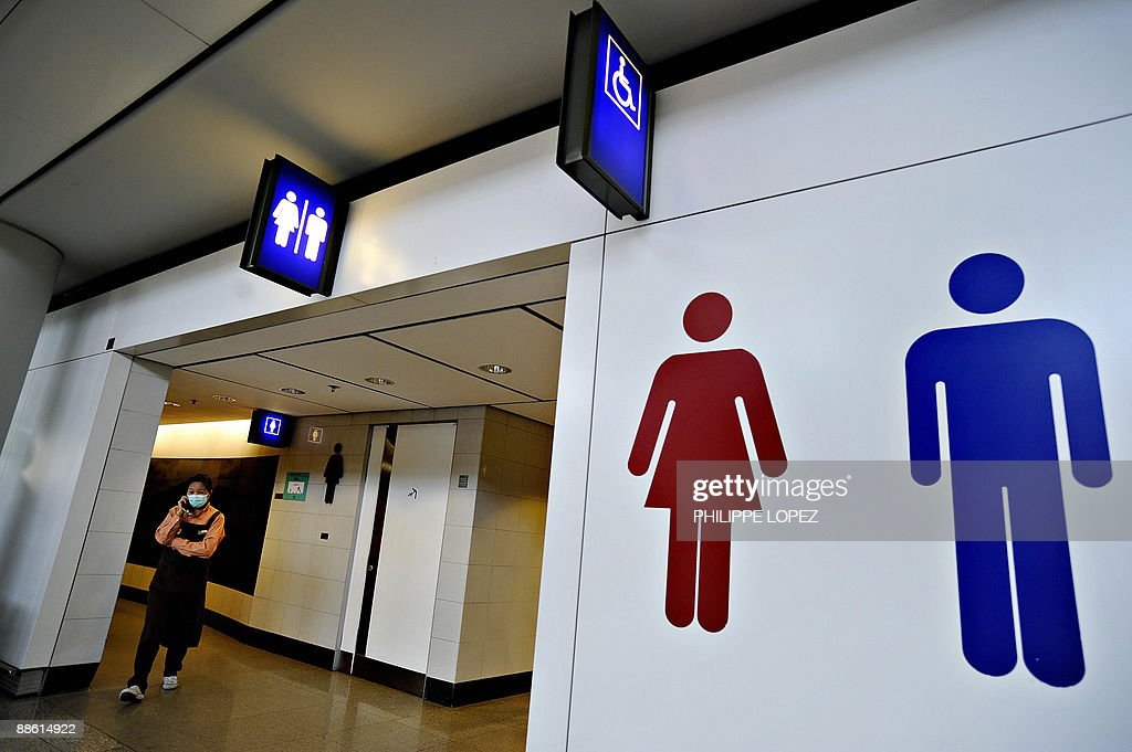A woman wearing a mask walks out of the toilets at the Hong Kong international airport on May 2 2009 The first confirmed case of swine flu in Asia...