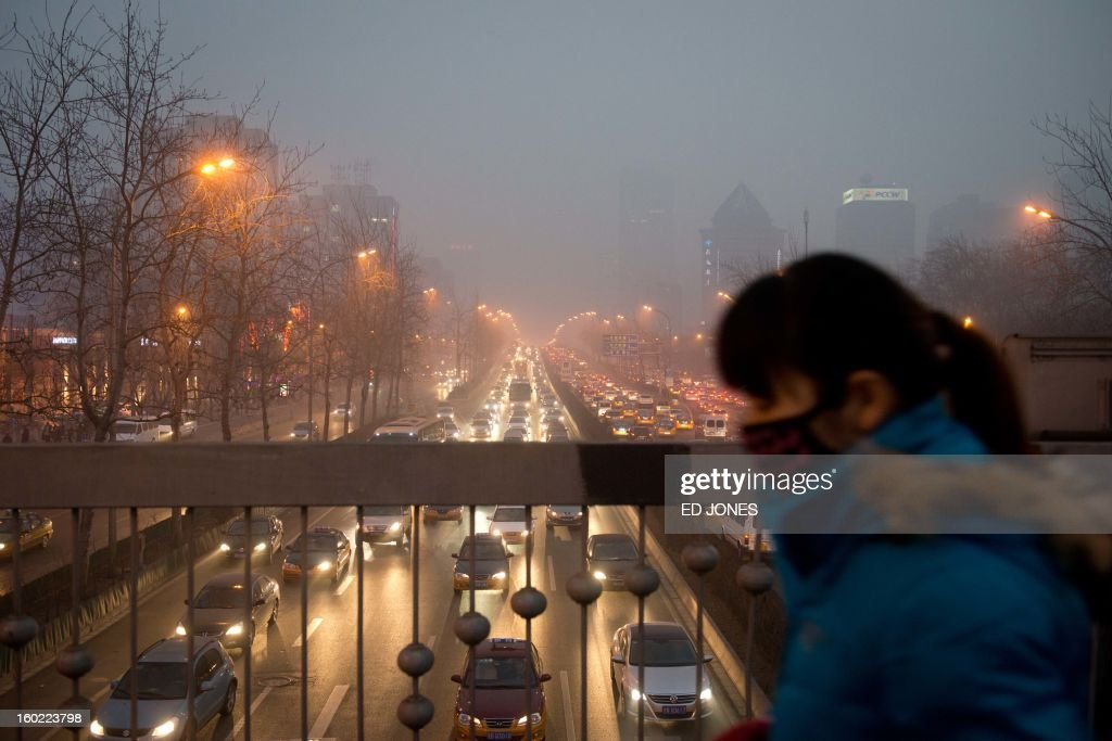 A woman wearing a mask walks over a road bridge in heavy pollution on January 28, 2013. The US embassy air quality index twitter feed recorded levels classed as 'hazardous', with a figure of 493 -- almost 20 times the World Health Organisation's safe limit. AFP PHOTO / Ed Jones