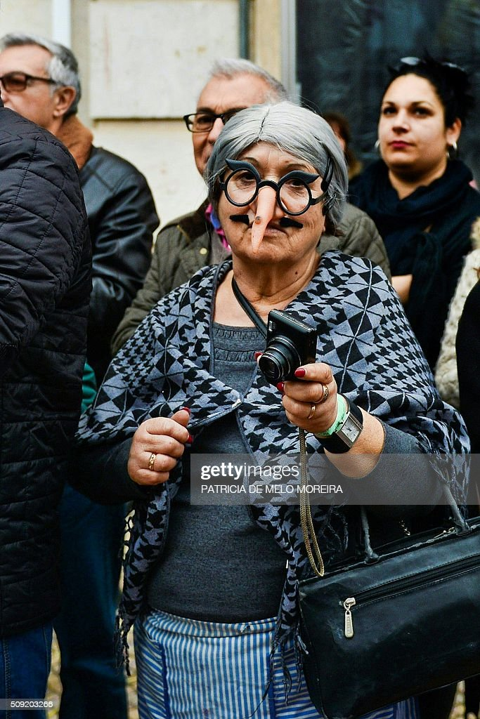 A woman wearing a mask watches the annual carnival parade in Torres Vedras on February 9, 2016. The Torres Vedras Carnival is allegedly the 'most Portuguese' of all the carnivals in the country recognized by the strong political and football satire of the revelers disguises and their floats. / AFP / PATRICIA DE MELO MOREIRA