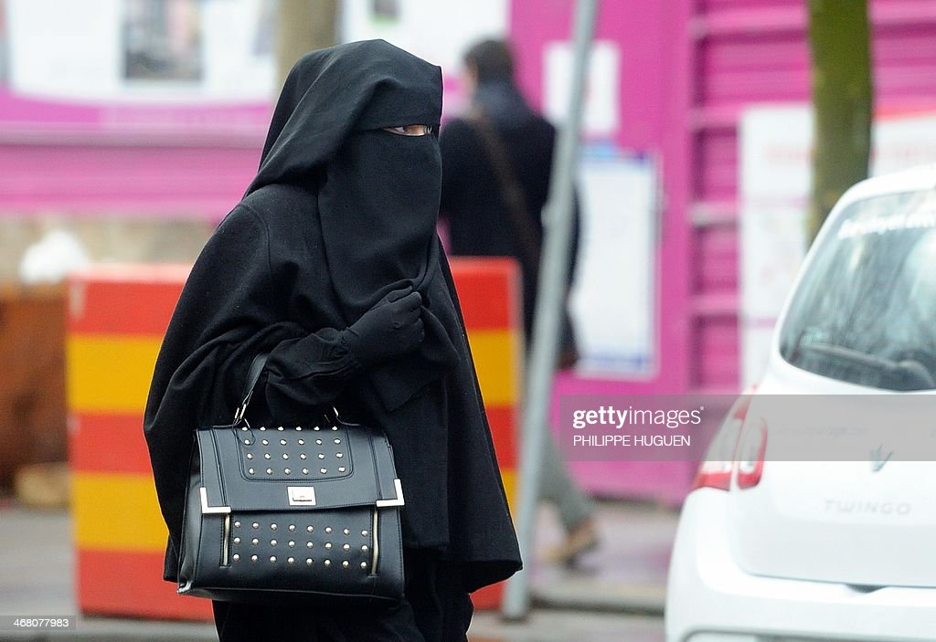 A woman wearing a niqab a type of full veil as she walks in a street in the center of Roubaix northern France on January 9 2014 AFP PHOTO / PHILIPPE...
