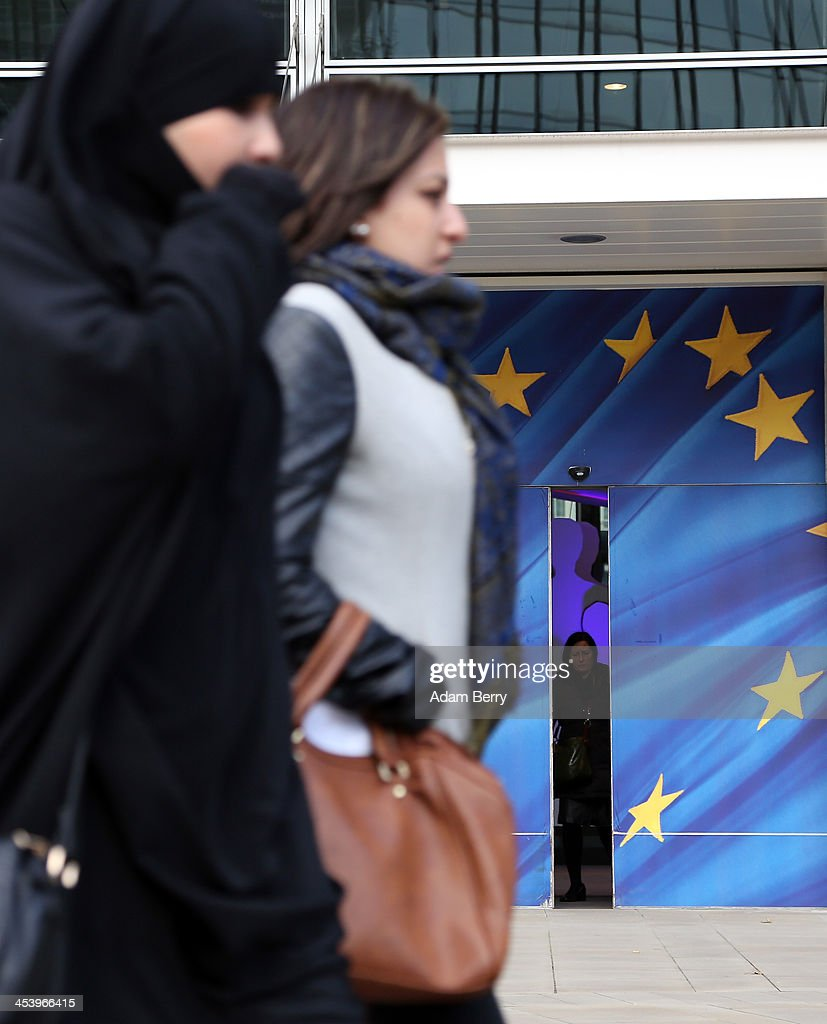 A woman wearing a niqab passes the Berlaymont building of the European Commission (EC) on December 6, 2013 in Brussels, Belgium. The European Commission is responsible for the implementation and maintenance of the execution of the European Union's policies.