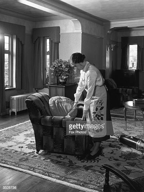 A woman wearing a patterned apron cleaning an armchair with a vacuum cleaner