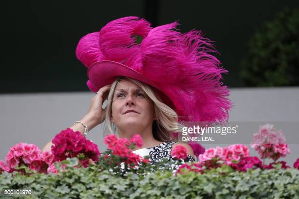 A woman wearing a pink featheradorned hat waits for the arrival of Britain's Queen Elizabeth II on the fourth day of the Royal Ascot horse racing...