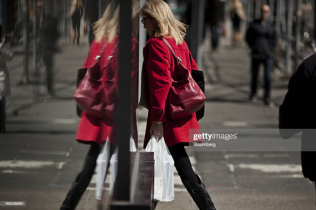 A woman wearing a red coat carrying a shopping bag enters a store in New York, U.S., on Thursday, April 4, 2013. Confidence among U.S. consumers stabilized last week, stemming a pullback in sentiment that had threatened to check recent gains in spending. Photographer: Victor J. Blue/Bloomberg via Getty Images