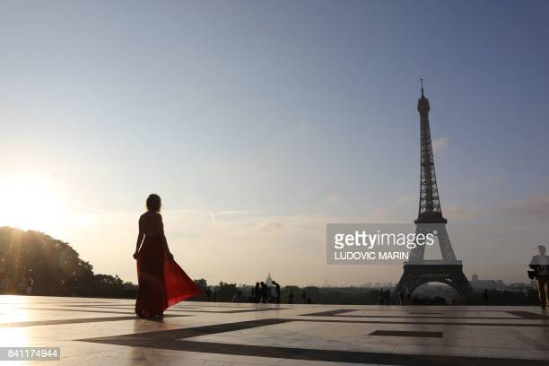 A woman wearing a red dress stands in front of the Eiffel tower on Trocadero plaza in Paris at sunrise on August 31 2017 / AFP PHOTO / LUDOVIC MARIN