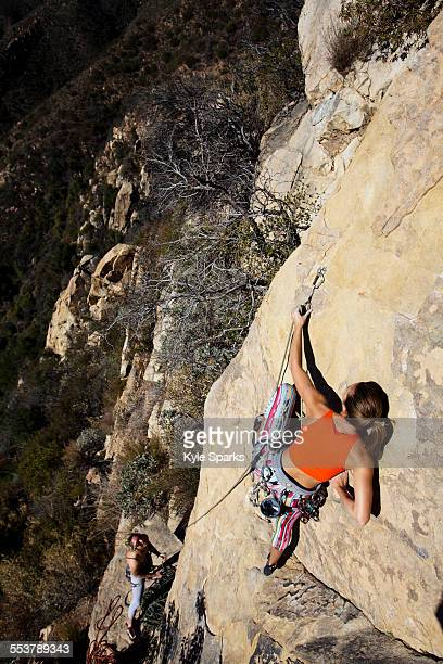 A woman wearing a red tank top and striped pants climbs The Rapture (5.8) on Lower Gibraltar Rock in Santa Barbara, California.