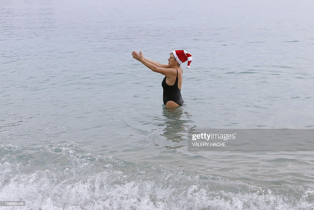 A woman wearing a Santa Claus hat enjoy a traditional Christmas bath on December 23, 2012 in Monaco. AFP PHOTO / VALERY HACHE