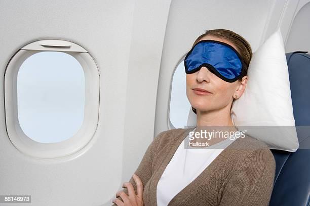 A woman wearing a sleep mask sleeping on a plane