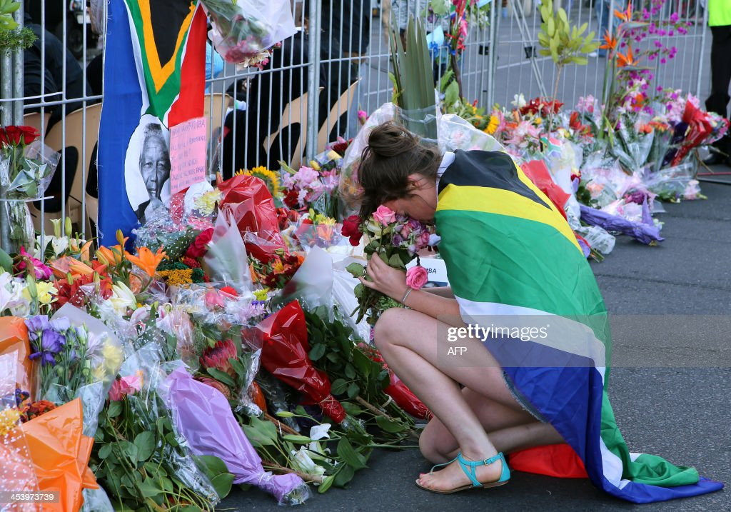 A woman wearing a South African flag holds flowers before laying them with others in front of a picture of late South African former president Nelson Mandela on December 6, 2013 during an inter-faith service held at the Grand Parade in Cape Town, where Mandela made his first speech as a free man in 1990. Mandela, the revered icon of the anti-apartheid struggle in South Africa and one of the towering political figures of the 20th century, died in Johannesburg on December 5 at age 95. Mandela, who was elected South Africa's first black president after spending nearly three decades in prison, had been receiving treatment for a lung infection at his Johannesburg home since September, after three months in hospital in a critical state.