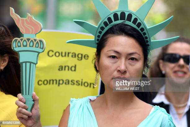A woman wearing a Statue of Liberty costume protests US President Donald Trump's immigration policies in Sydney's Martin Place on March 9 2017 / AFP...