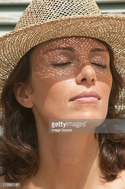 Woman wearing a sun hat with eyes closed